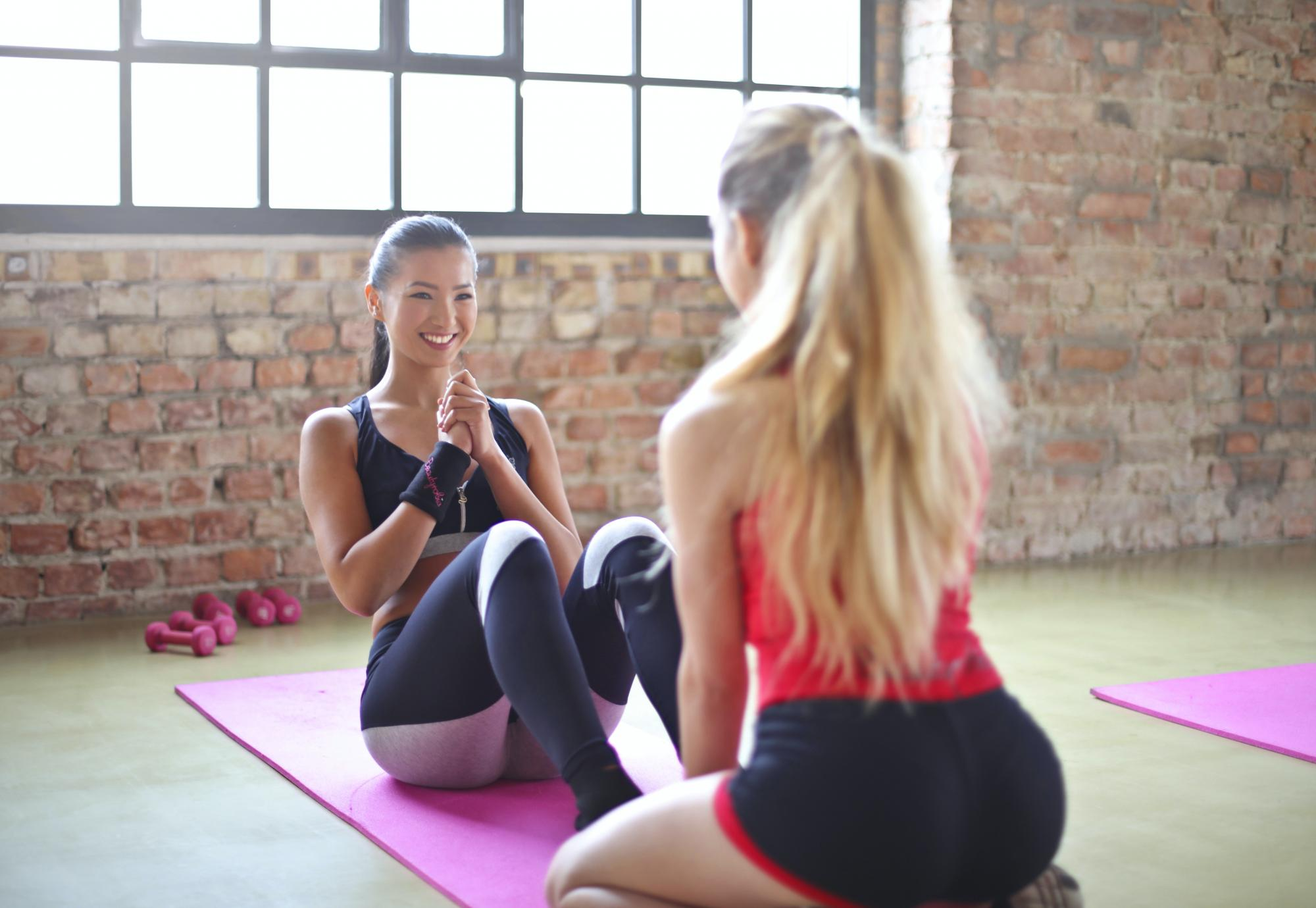 women sitting on yoga mat